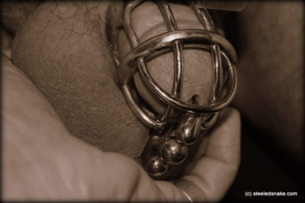man in cock cage chastity device