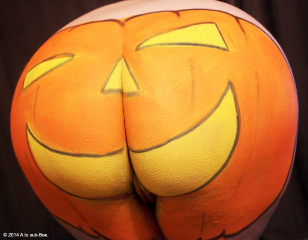 pumpkin face paints onto womans bottom for Halloween