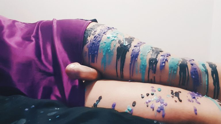 different coloured wax dripped onto womans legs, wax play