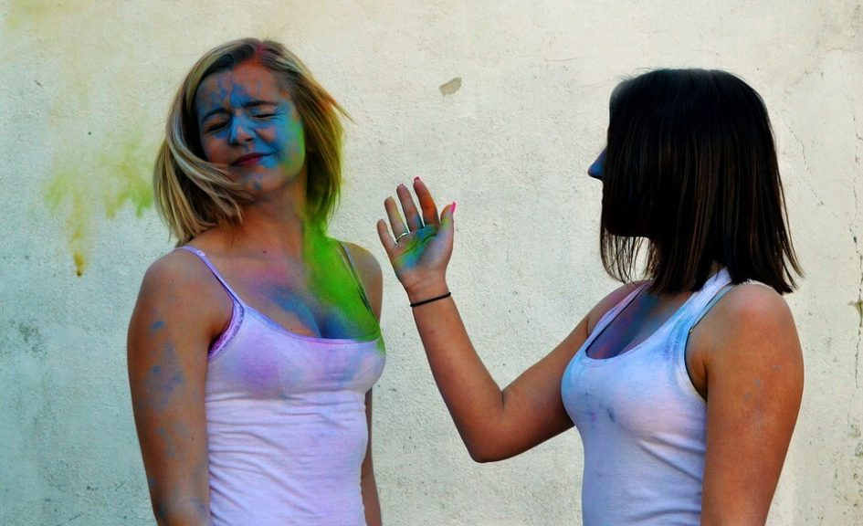woman slapping other woman's face with coloured powder