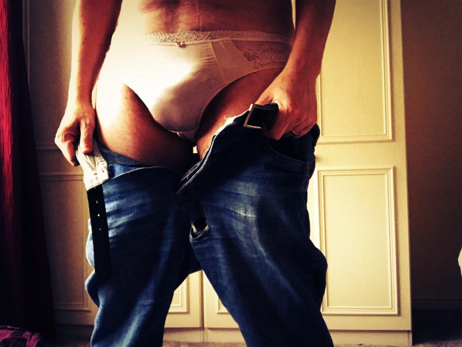 man lowering his jeans to reveal he is wearing panties