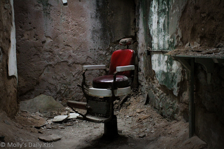 Old barbers chair in deralict prison for post about kink for things and places