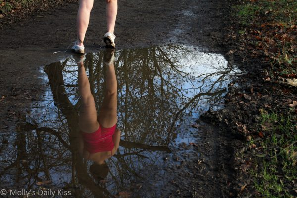 Reflection of woman running for post about exercise as a kink